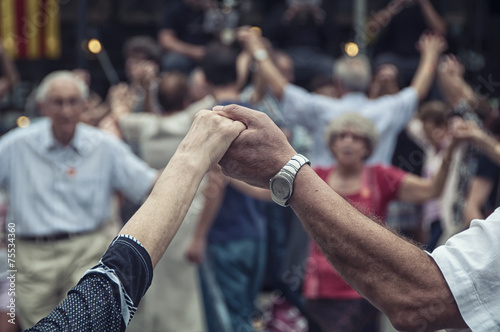 Leinwanddruck Bild senior people holding hands and dancing national dance Sardana