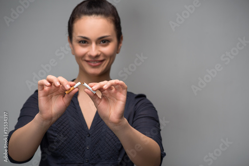 Addiction. Closeup of young attractive woman breaking cigarettes - 75534397