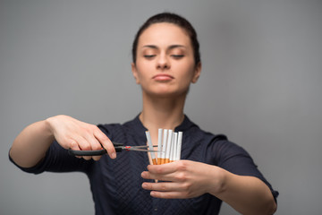 Stop smoking concept. Young woman cut cigarettes with scissors s