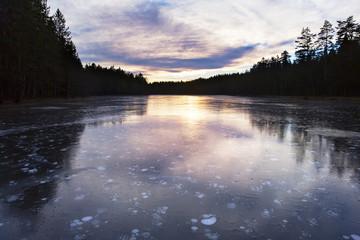 Idyllic and icy lake in sunset