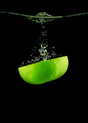 Half a lime falling into the water