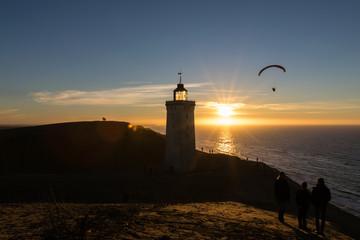 Paraglider und Leuchtturm im Sonnenuntergang