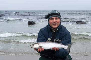 Happy angler with winter sea trout