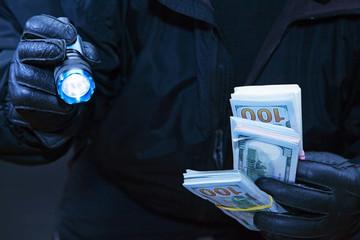 Thief steals money in darkness