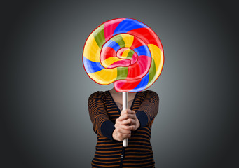 Young woman holding a lollipop