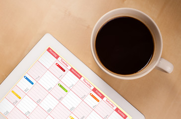 Tablet pc showing calendar on screen with a cup of coffee on a d