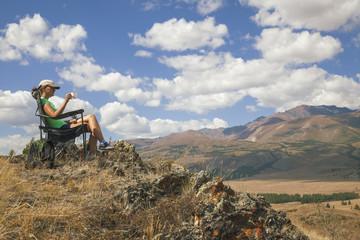 Happy tourist girl on the mountain