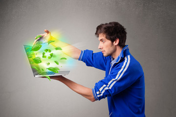 Casual boy holding laptop with recycle and environmental symbols