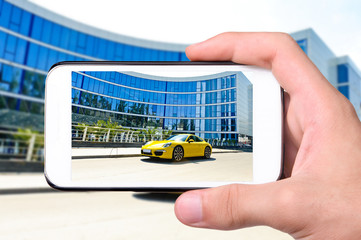 Hands taking photo car with smartphone