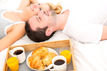Portrait of a couple having breakfast in bed