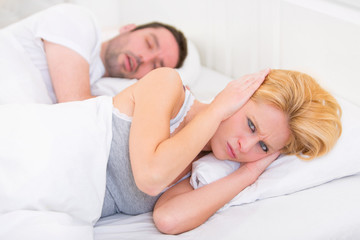 Young woman can't sleep because of boyfriend's snoring