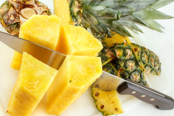 Cutting fresh pineapple with kitchen knife