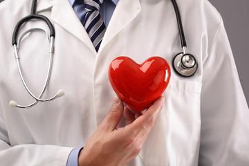 Doctor holding heart against chest