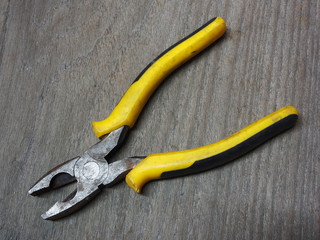 A yellow pliers on wooden board