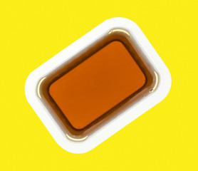 Maple syrup in a plastic container on a yellow background