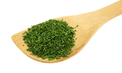 Parsley flakes on a wood spoon
