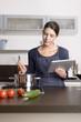 canvas print picture - Hausfrau liest ein Rezept auf dem Tablet Computer