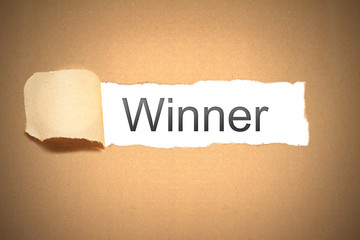 brown paper torn to reveal winner