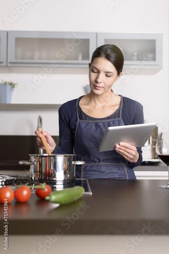canvas print picture Hausfrau liest ein Rezept auf dem Tablet Computer