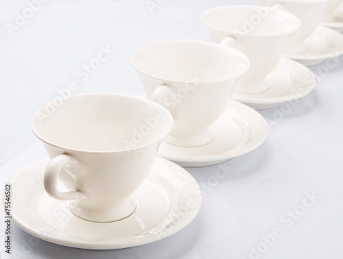 Ceramic saucer and teacup over white background  - 75546502