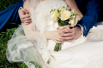Wedding bouquet of roses and daisies in the hands of the newlywe