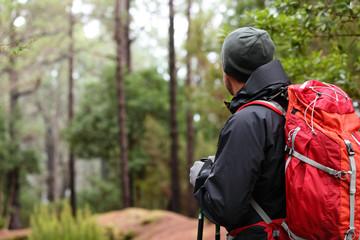 Hiker wearing hiking backpack and hardshell jacket
