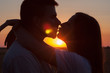 Silhouettes of couple kissing at summer sunset