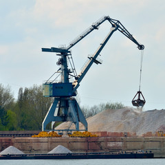 Crane loading industrial cargo ship with gravel