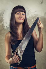 beautiful young girl holding saw over grunge background