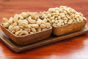 Cashew nuts and peanuts in wooden bowl.