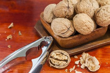 Walnuts in a wooden bowl with nutcracker on table