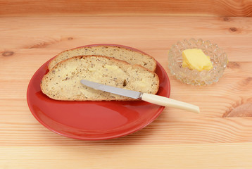 Buttered slices of bread on a red plate