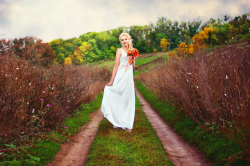 Beautiful bride posing outdoors with a bouquet