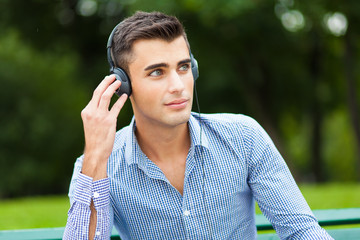 Young man listening to music in a city park