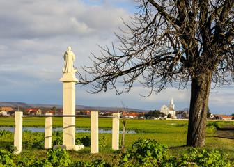 Bildstock am Land mit Kirche im Hintergrund