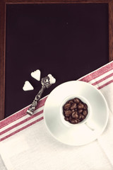 top view over  coffee beans in cup and sugar on black chalkboard