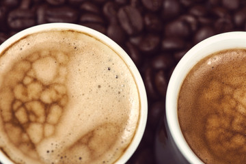 Fresh creamy expresso over roasted coffee beans background