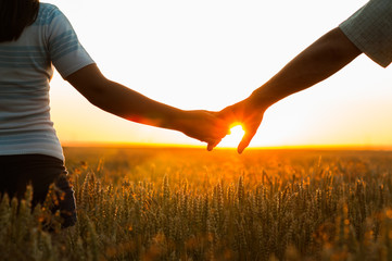 Young couple holding hands in the wheat field on sunny summer da