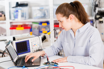 Woman  with a tester and a printed circuit board