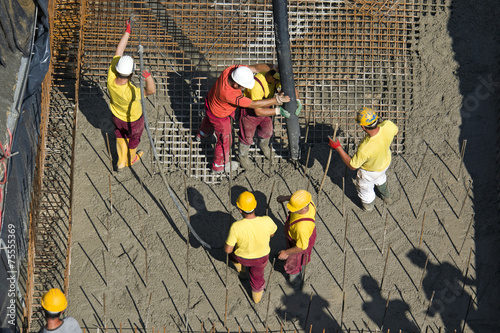 Construction workers casting foundations of hydro power plant - 75555369
