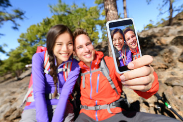 Selfie couple using smart phone hiking in nature