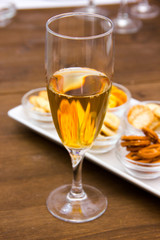 Flute with aperitif and pretzels on wooden table seen close