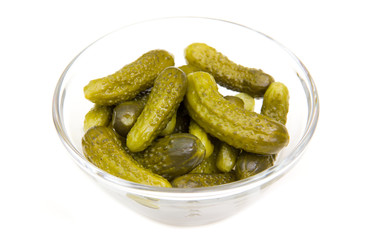 Pickled cucumbers on glass bowl on white background
