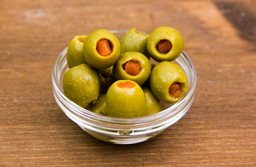 Stuffed olives in bowl on wooden table