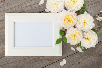 Blank photo frame and white roses