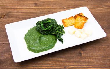 Tray with creamed spinach and croutons on wooden table