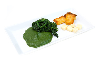 Tray with creamed spinach and croutons on a white background