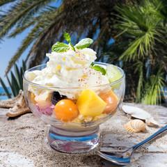 Eisbecher mit tropischen Früchten unter Palmen am Meer