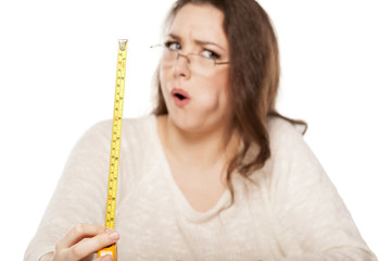 young woman is stunned by the size shown on the measuring tape