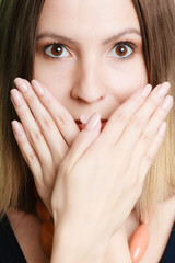 Surprised woman face covering her mouth with hands